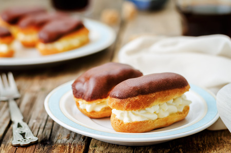 chocolate background: eclairs with cheese cream and chocolate glaze on a dark wood background