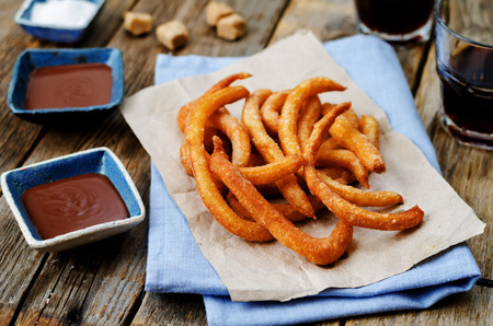 calorie rich food: churros with chocolate sauce on a dark wood background. toning. selective focus
