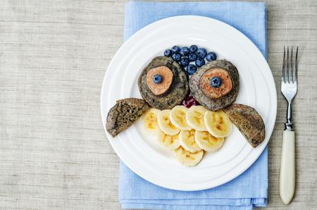 comidas saludables: panqueques de chocolate de arándanos con plátanos en la forma de un búho para los niños. viraje. enfoque selectivo Foto de archivo