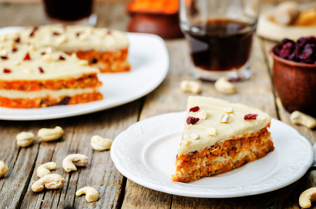 riches: raw vegan carrot cake with cashew cream and dried cranberries. toning. selective focus Stock Photo