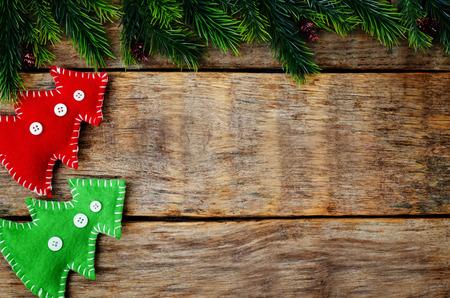 botas de navidad: wood background with Christmas tree and homemade fleece toys. toning. selective focus
