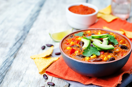 Chipotle red bean tortilla soup on a white wood background. toning. selective focus
