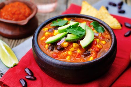Chipotle red bean tortilla soup on a dark wood background. toning. selective focus Stockfoto