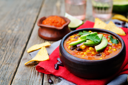 indian food: Chipotle red bean tortilla soup on a dark wood background. toning. selective focus Stock Photo