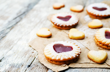 Shortbread with the shape of a heart and berry jam on a white wood background.