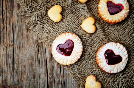 Shortbread with the shape of a heart and berry jam on a dark wood background.