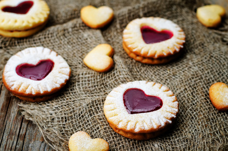 jam tarts: Shortbread with the shape of a heart and berry jam on a dark wood background.