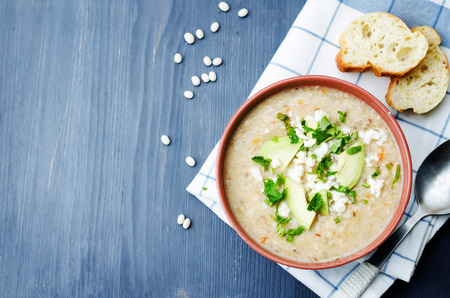 White beans chicken soup on a dark wood background. Stockfoto