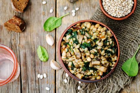 spinach, white beans barley porridge on a dark background.