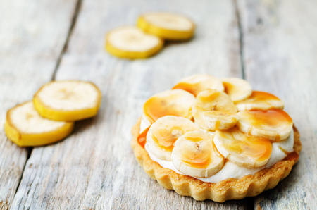 tartlet: banana salted caramel tartlet on a white wood background. toning. selective Focus Stock Photo