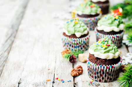 chocolate sprinkles: Chocolate cupcakes with green frosting and sprinkles on holiday. toning. selective Focus