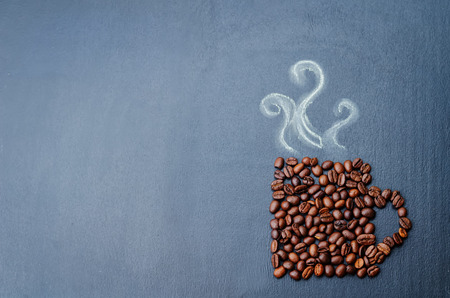 coffee beans in the form of cup of coffee on the chalkboard. toning. selective Focus Banco de Imagens