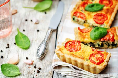 baked bread: spinach, tomatoes, mushroom quiche on a white wood background. toning. selective Focus