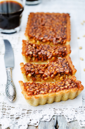 calorie rich food: honey pine nuts tart on a white wood background. toning. selective Focus