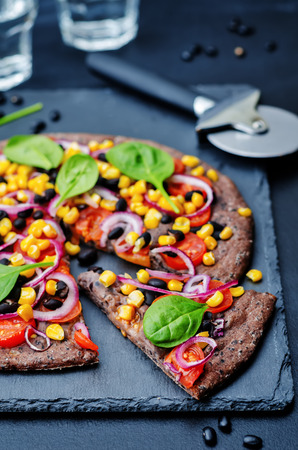 black beans: Black beans crust pizza with corn, spinach, tomatoes, black beans and red onion on black background. toning. selective Focus Stock Photo