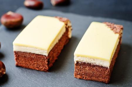 queso blanco: brownie de castañas con la castaña mousse de chocolate blanco sobre un fondo negro. viraje. Enfoque selectivo