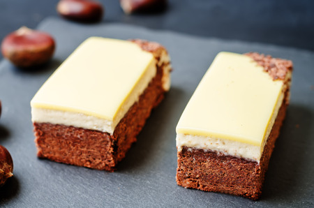 white chocolate: chestnut brownie cake with chestnut  white chocolate mousse on a black background. toning. selective Focus Stock Photo