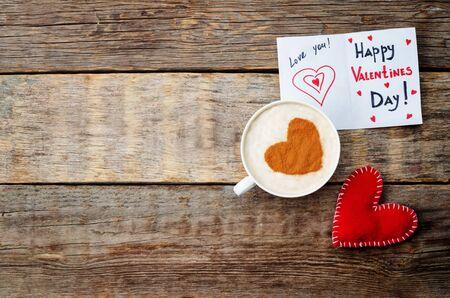 Karte für Valentinstag, rotes Spielzeug-Herz und eine Tasse Kaffee auf einem dunklen Holz Hintergrund. Tonen. selektiven Fokus