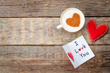 card for Valentines day, red toy heart and a cup of coffee on a dark wood background. toning. selective Focus Reklamní fotografie