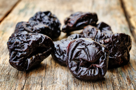tinting: prunes on a dark wood background. tinting. selective focus