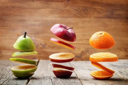 apfel: Fruchtscheiben fliegen: Apfel, Birne, Orange auf dunklem Holz Hintergrund. Tonen. selektiven Fokus