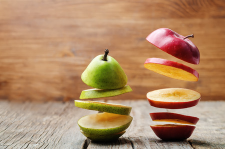 flying slices of fruit: apple, pear on a dark wood background. toning. selective Focus