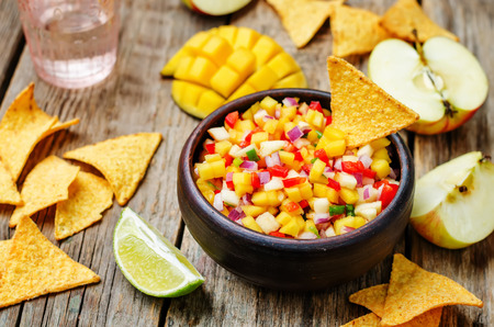 tortilla chips: apple mango salsa on a dark wood background. toning. selective Focus Stock Photo