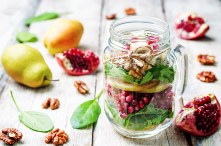 a pomegranate: homemade pear, spinach, walnuts, pomegranate, blue cheese salad in a glass jar. toning. selective Focus