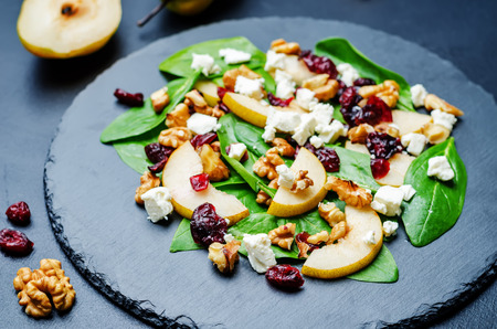 spinach, dried cranberries goat cheese walnuts pear salad on a black background. toning. selective Focus
