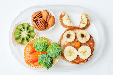 aliments droles: school lunch box for kids with food in the form of funny faces. the toning. selective focus