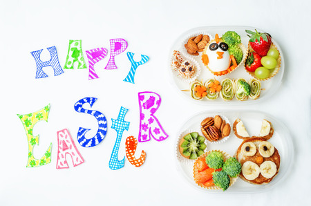 school form: Happy Easter words with school lunch boxes for kids with food in the form of funny faces. the toning. selective focus Stock Photo