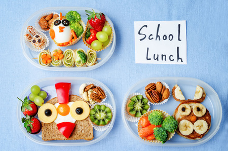 to lunch: caja de almuerzo escolar para los ni�os con los alimentos en forma de caras divertidas. la tonificaci�n. enfoque selectivo Foto de archivo