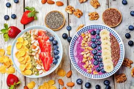 licuado de platano: Arándanos y fresas cuencos batidos saludables para el desayuno con frutos secos, semillas y frutas. viraje. enfoque selectivo