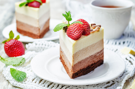 three chocolate cake decorated with strawberries and mint leaves. toning. selective focus Imagens