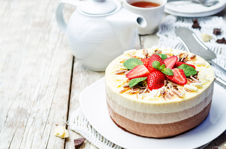 three chocolate cake decorated with strawberries and mint leaves. toning. selective focus Stock Photo