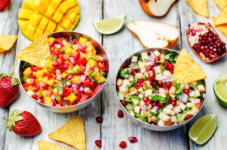 chips and salsa: pomegranate pear and strawberry mango pepper salsa. toning. selective focus