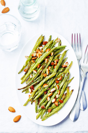 snap bean: roasted snap green beans with almond on a white background. toning. selective focus Stock Photo