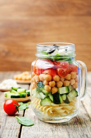 Pasta chickpeas cucumber tomatoes spinach goat cheese salad in a jar. toning. selective focus Stock Photo