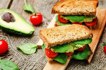 smashed: Smashed avocado spinach tomato grilled rye sandwich. toning. selective focus Stock Photo