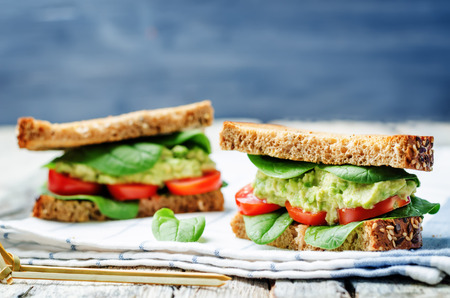 Smashed avocado spinach tomato grilled rye sandwich. toning. selective focus 版權商用圖片
