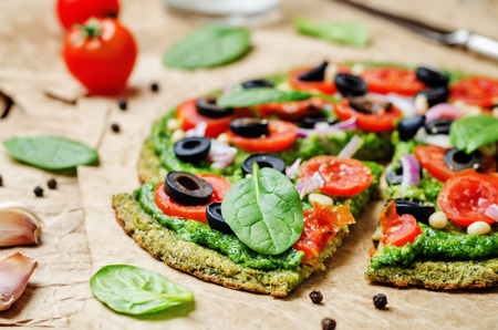 pizza crust: vegan broccoli zucchini pizza crust with spinach pesto, tomatoes, onion and olives. toning. selective focus
