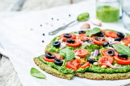 ビーガンほうれん草ペスト、トマト、タマネギ、オリーブとズッキーニのピザ生地をブロッコリー。調子を整えます。選択と集中 写真素材