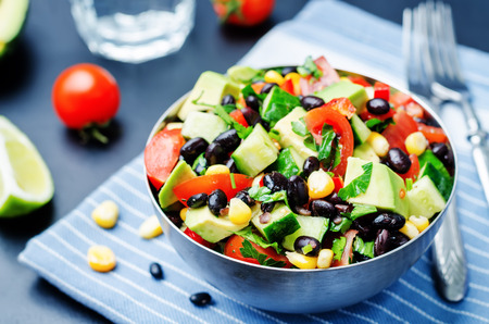 black bean: Black beans corn avocado cucumber tomato salad with lime dressing. toning. selective focus