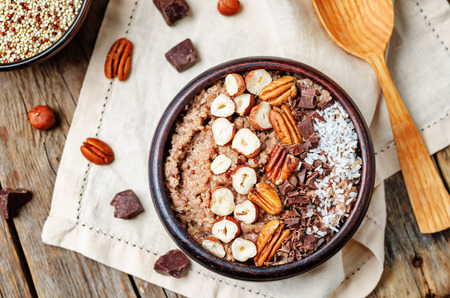 breakfast bowl: Chocolate Quinoa breakfast bowl decorated with hazelnuts, Pecan, chocolate and coconut. toning. selective focus Stock Photo