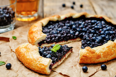 Blueberry galette on a dark wood background. toning. selective focus Imagens