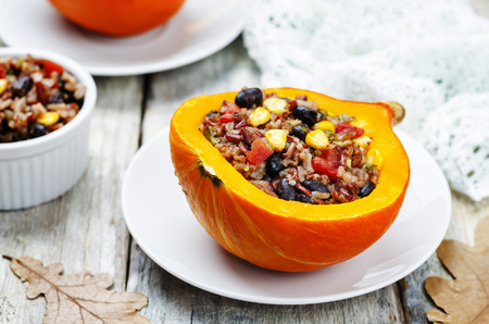 black beans corn white and red rice stuffed pumpkin. toning. selective focus Stock Photo