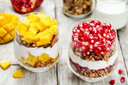list of Greek yogurt granola parfait. Pomegranate and mango. toning. selective focus