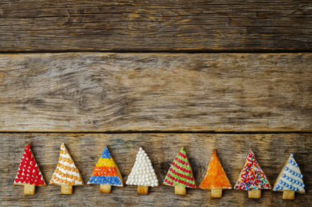 decorate: colored Christmas tree cookies on a dark wood background. toning. selective Focus