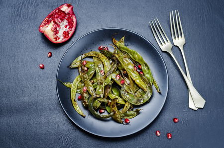 snap bean: roasted snap green beans with Pomegranate on a black background. toning. selective focus