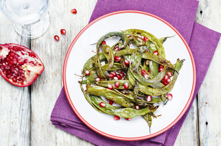 snap bean: roasted snap green beans with Pomegranate on a white wood background. toning. selective focus
